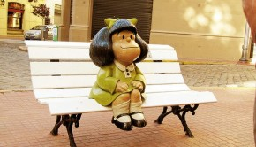Mafalda, an iconic Argentine cartoon character by the graphic artist Quino, sits on a bench in front of Quino's childhood home in San Telmo, a bohemian neighborhood ideal for both guided tours and independent exploration.