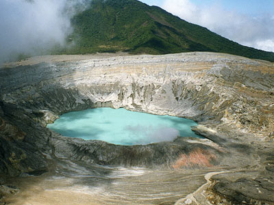 Sulfuric fumaroles burst upwards to ruffle the surface of ethereal crater lake of the Poás Volcano.