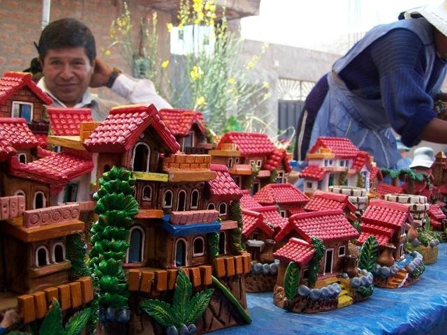 A local business man sells ceramic houses during the Festival de la Alasitas in Puno, Peru