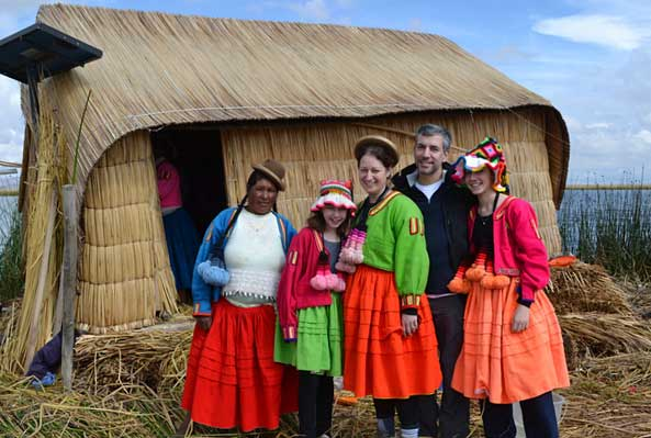 The Millers don traditional indiginous clothing and pose with an Uros woman on a floating island
