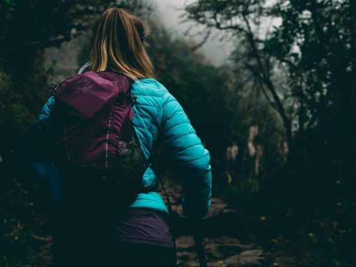 A woman wearing a jacket and carrying a backpack as she hikes on the Inca Trail to Machu Picchu.