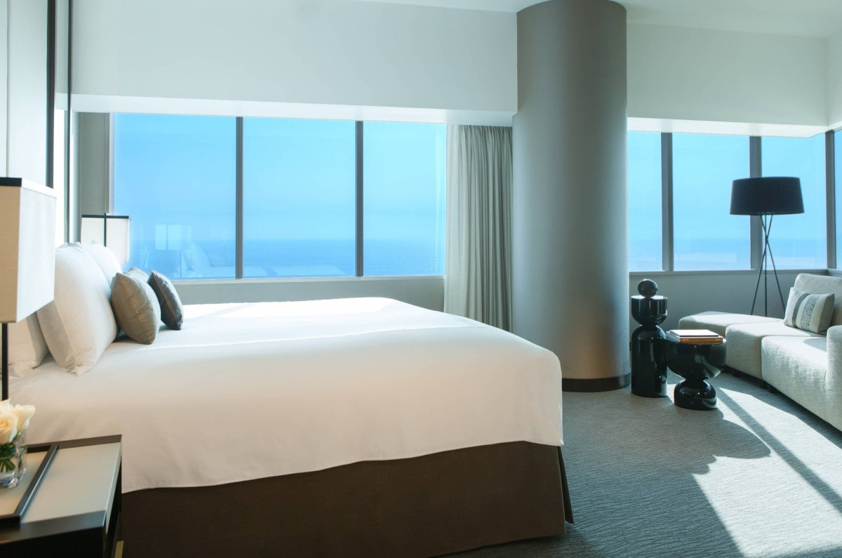 A bed and sitting area with ocean views beyond a wall of windows at JW Marriott in Lima.