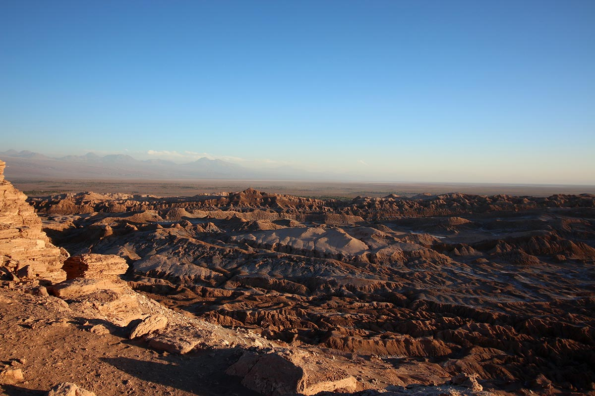 Rocky, uneven terrain stretches to the horizon below a bright blue sky.