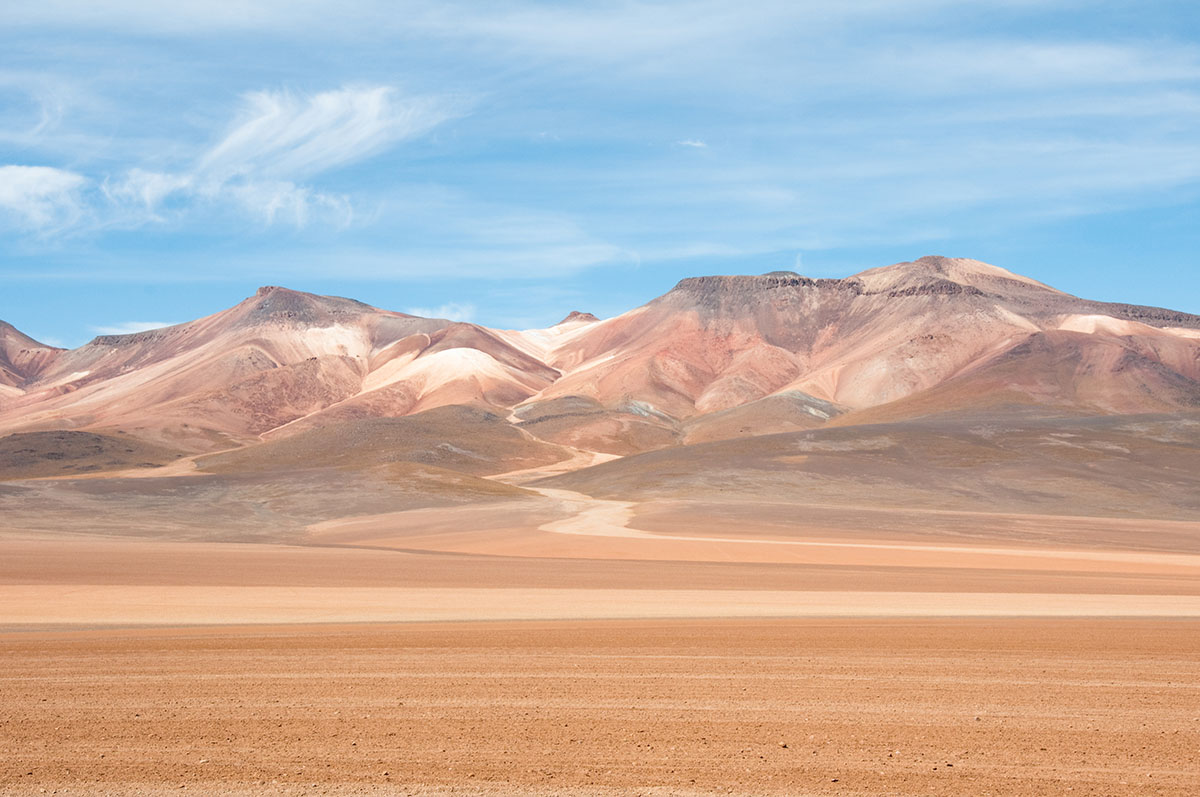 Orange and beige sands stretch to several rocky hills under a blue, cloudy sky in the Atacama Desert in South America.
