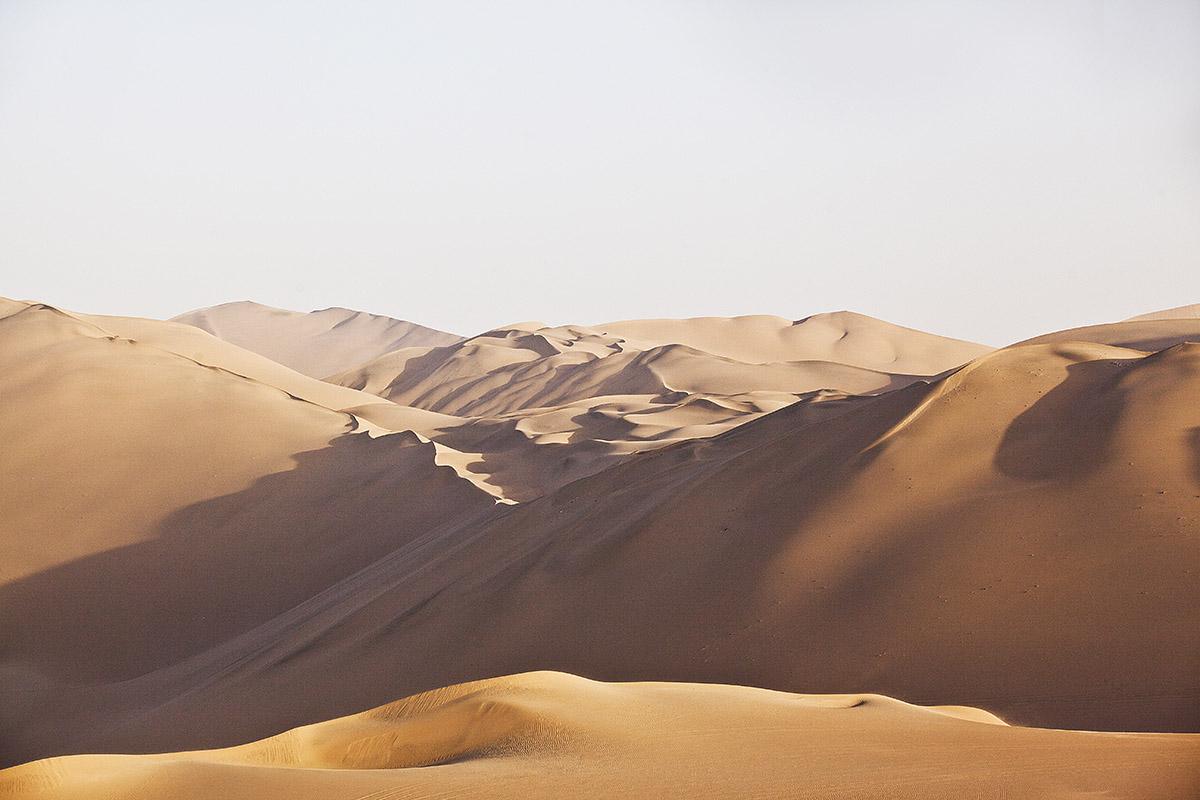 Hilly orange sand dunes under a white sky in the Peruvian Coastal Desert in South America.