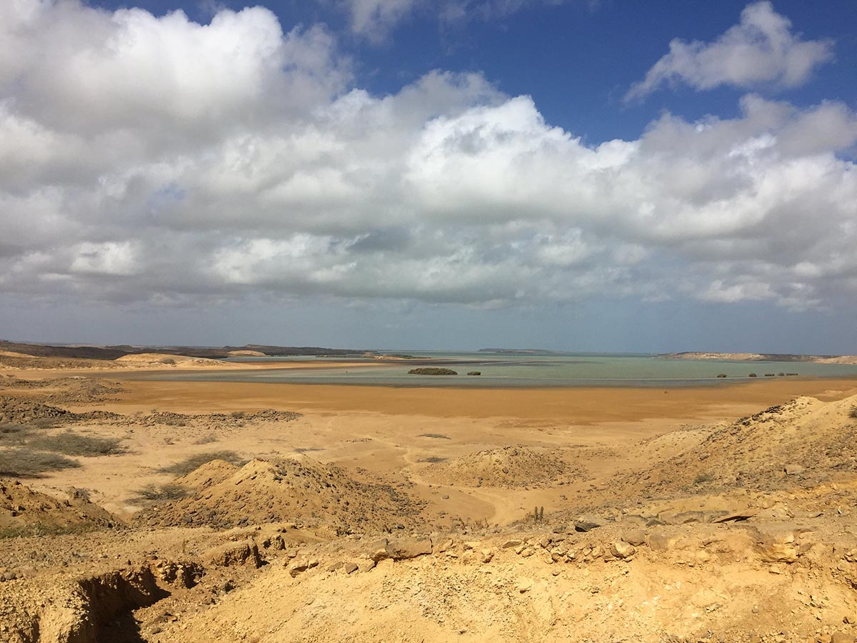 Barren, gold terrain leading to the horizon under cloudy, blue sky in the Guajira Desert of South America.