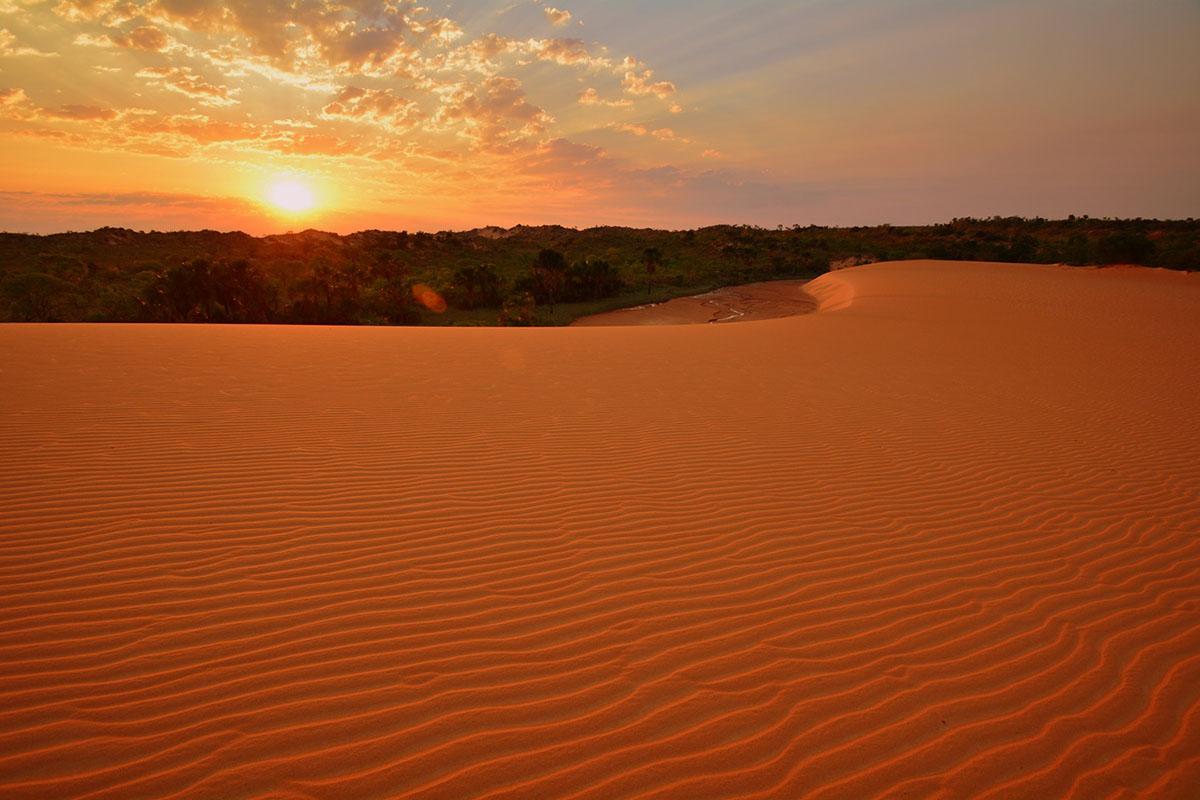 Sunset over deep orange dunes in the Jalapão Desert in South America.