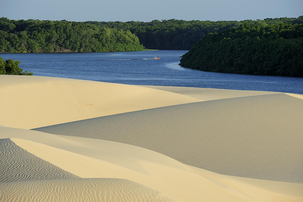 Beige sand dunes back up to a blue river with lush green trees on the other side.