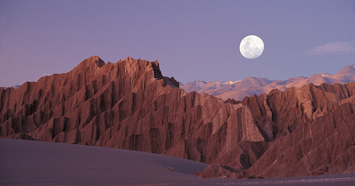 A full moon rises in a purple sky above mountainous rock formations in the Atacama Desert.