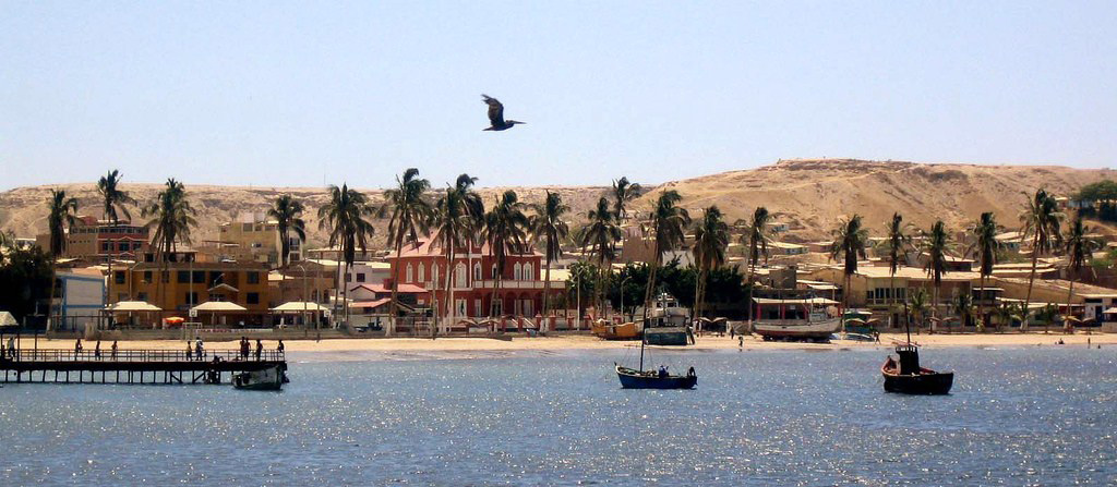 Boats and docks in the Pacific Ocean with several buildings and palm trees on the land. Sandy desert terrain in the background.