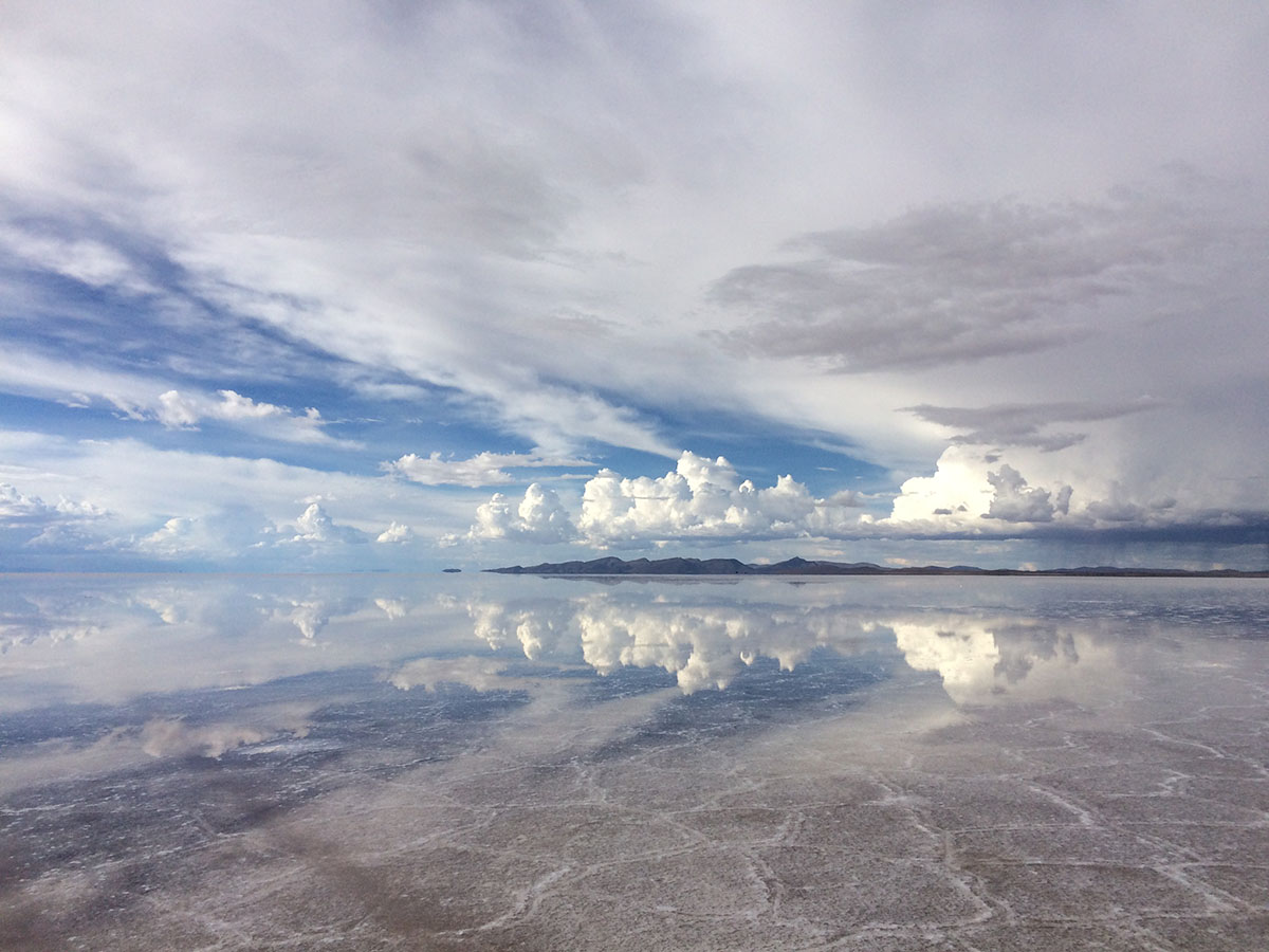 A cloudy sky reflected into the salt flats on the ground at the Uyuni desert.