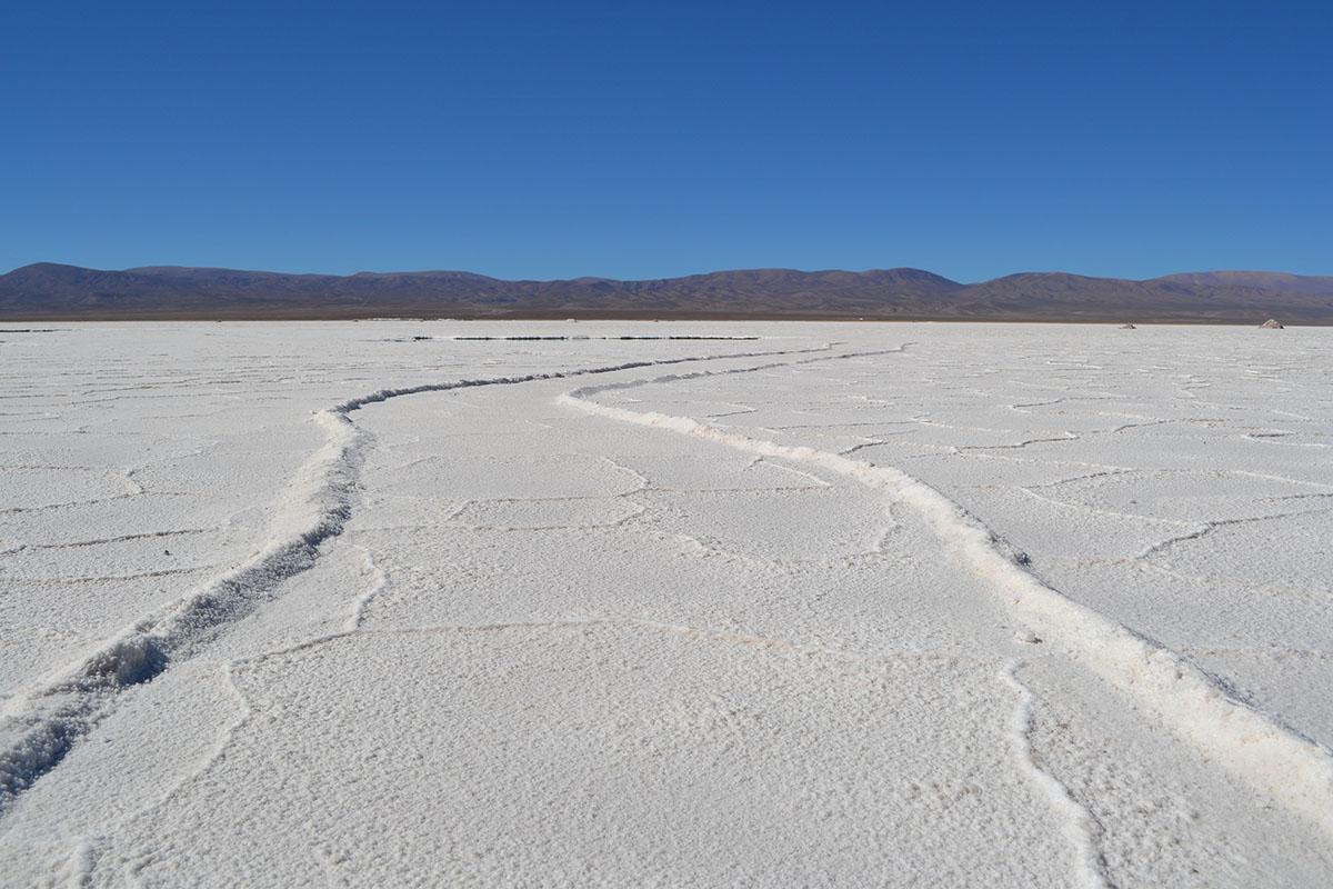 White salt stretches to dark, shallow mountains under blue skies in the Salinas Grandes of Argentina.