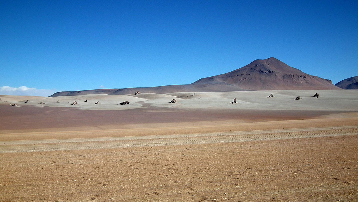 A barren, sandy desert with a mountain in the horizon under blue skies.