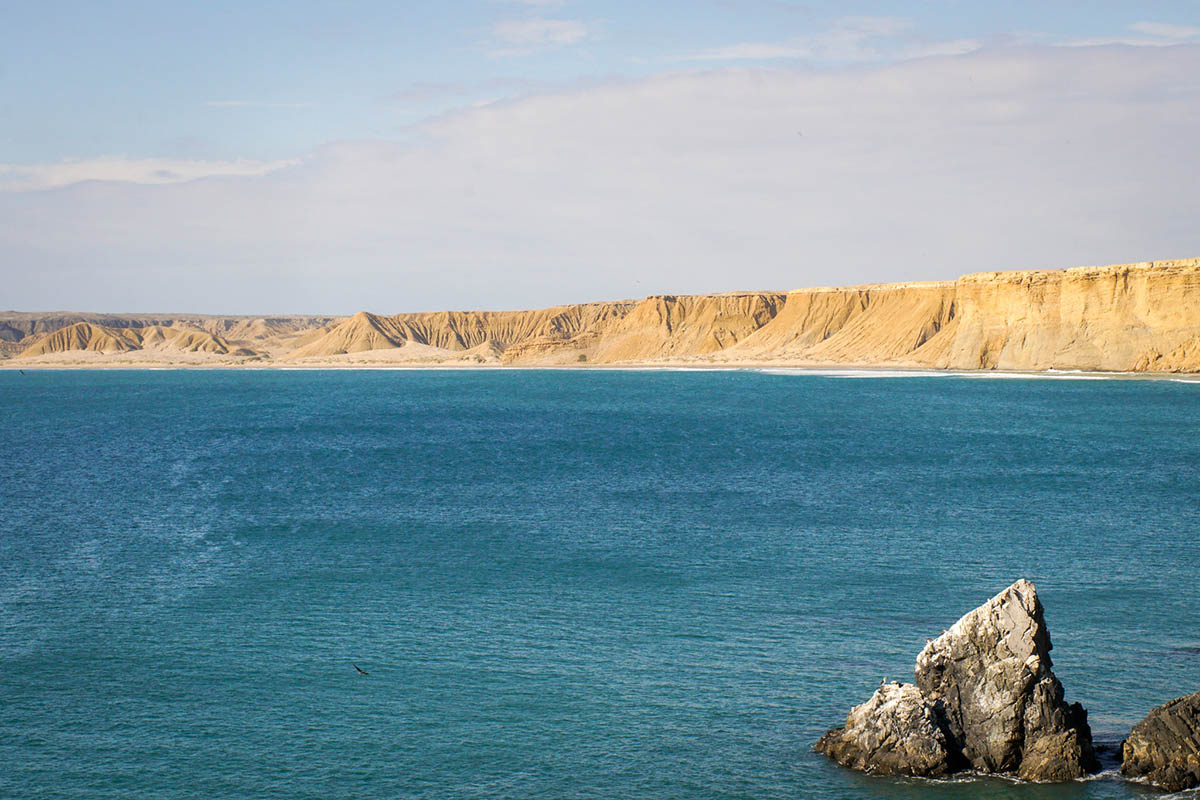 Blue ocean leading to sandy cliffs of the Sechura Desert in South America.