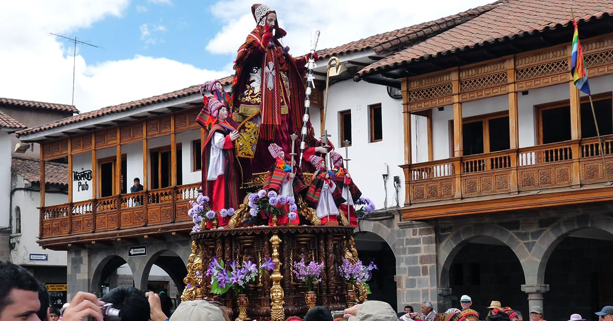A procession makes its way past some historic buildings with balconies at Corpus Christi in Cusco.
