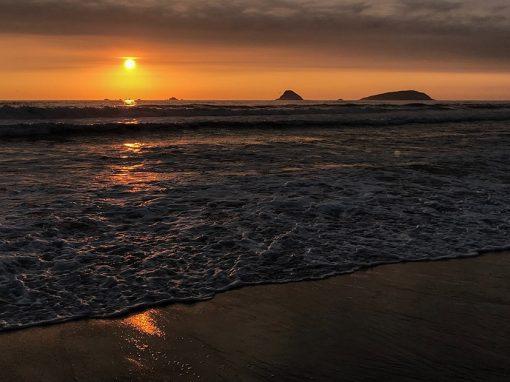 The setting sun turns the sky orange over the Los Pulpos beach on the Peruvian coast.