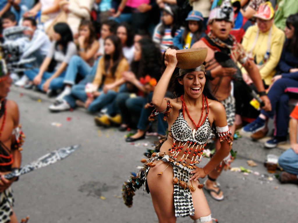 A woman dancing in a parade with a beaded and feathered traditional Amazonian outfit.