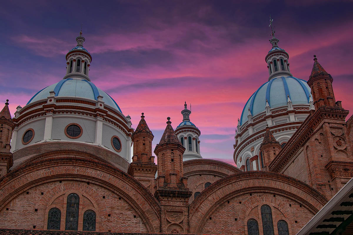 A brown church with blue domes on top and a pinkish-purple sunset behind in Cuenca, Ecuador.