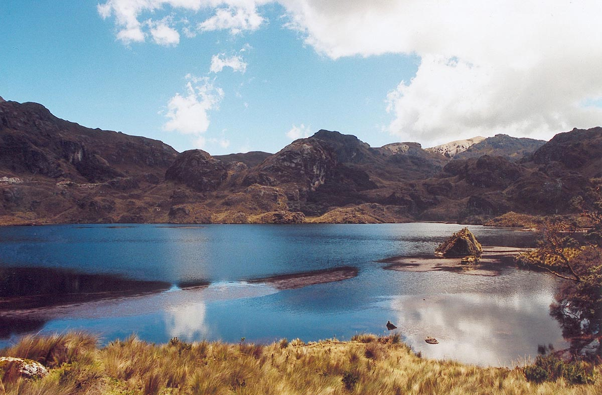 A shallow blue lagoon surrounded by brown rocky terrain in the El Cajas National Park.