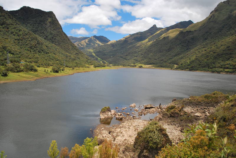 Lake Papallacta, a blue lagoon nestled between several small hills covered in green vegetation.