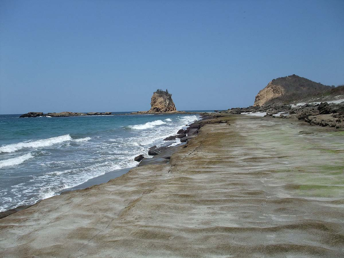 A long sandy beach with rock formations on the land and in the water at Machalilla National Park.