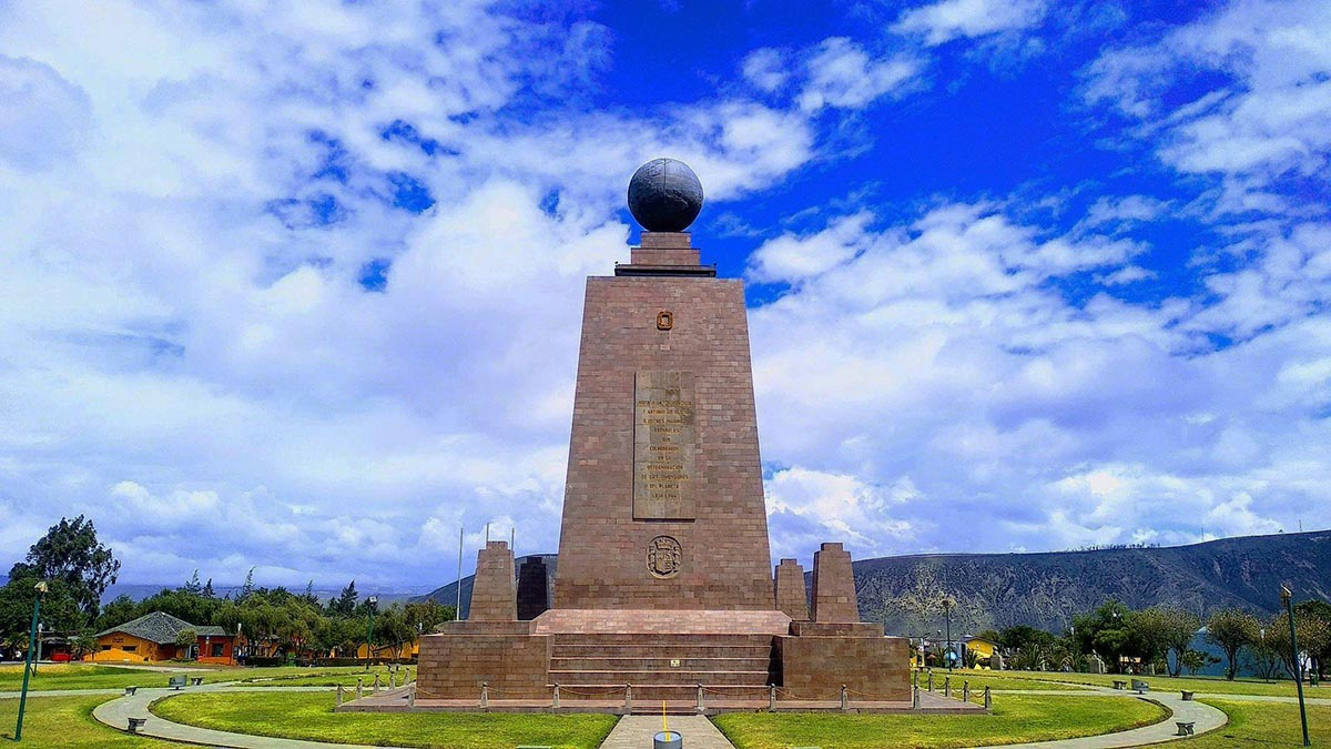 A tall stone monument with a globe placed on top at the equatorial line in Ecuador.