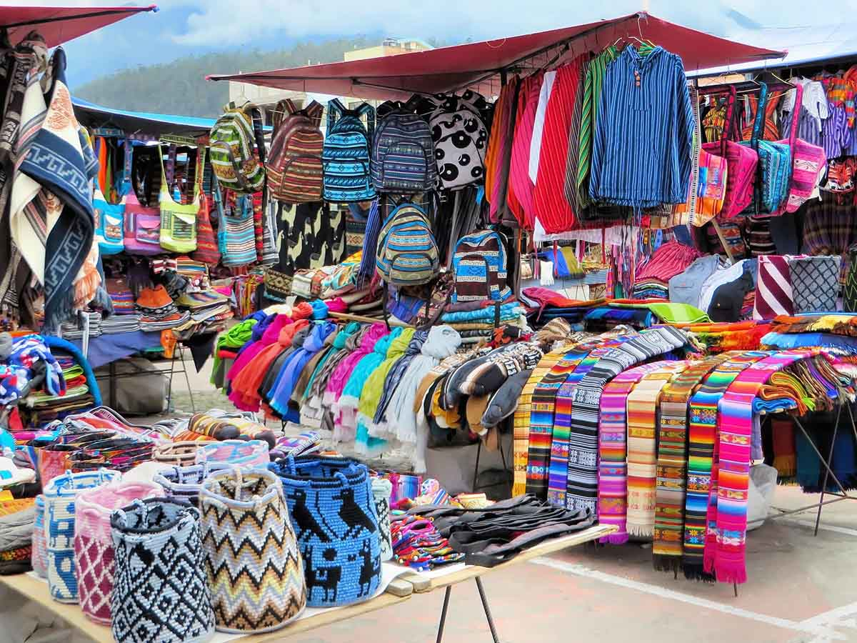 A colorful market stall selling various apparel and accessories like scarves, bags and ponchos.