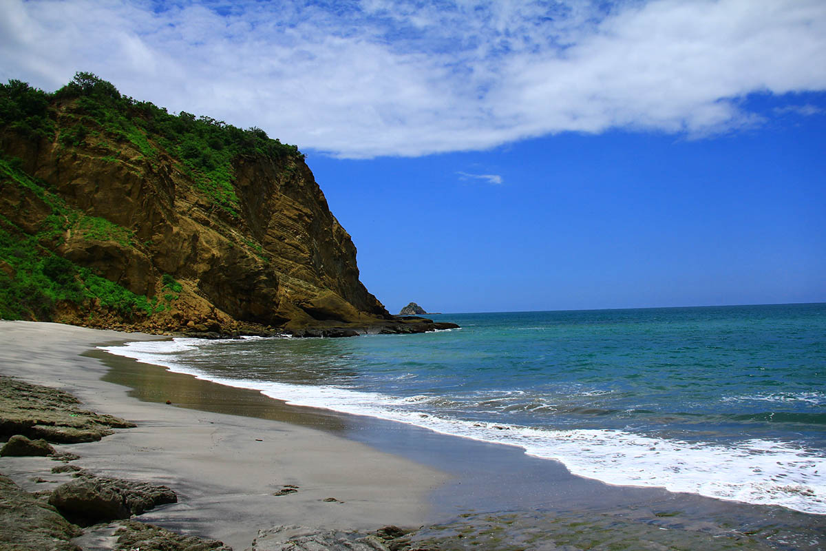 A sandy beach with rocky cliffs beyond the sandy area. Bright blue ocean and skies.
