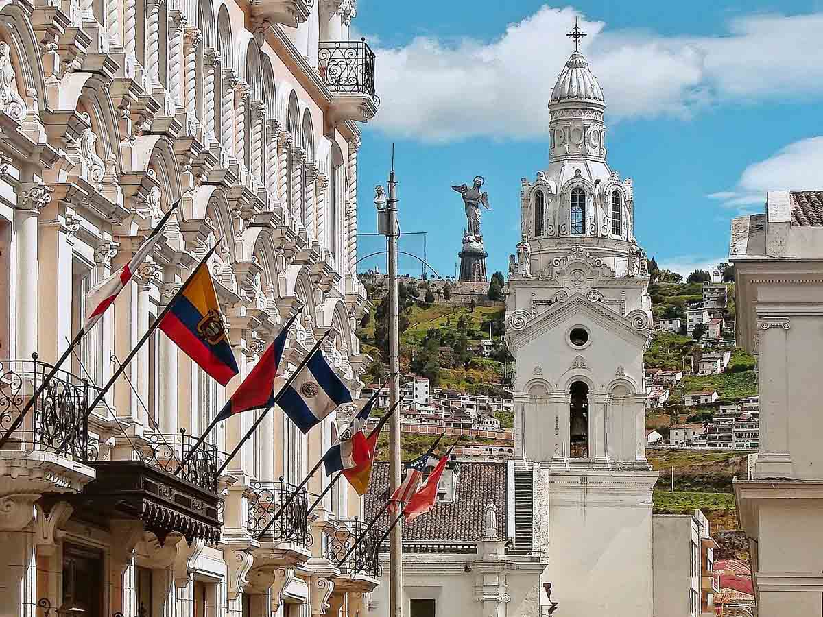 White stone building with flags sits next to a path leading to the Quito Metropolitan Cathedral.