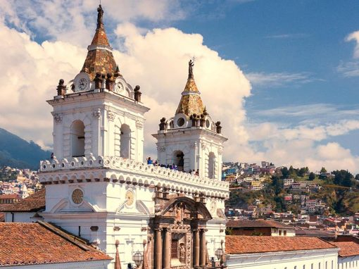 A white church, the San Francisco Monastery in Quito, with brown roof and accents and two spires.