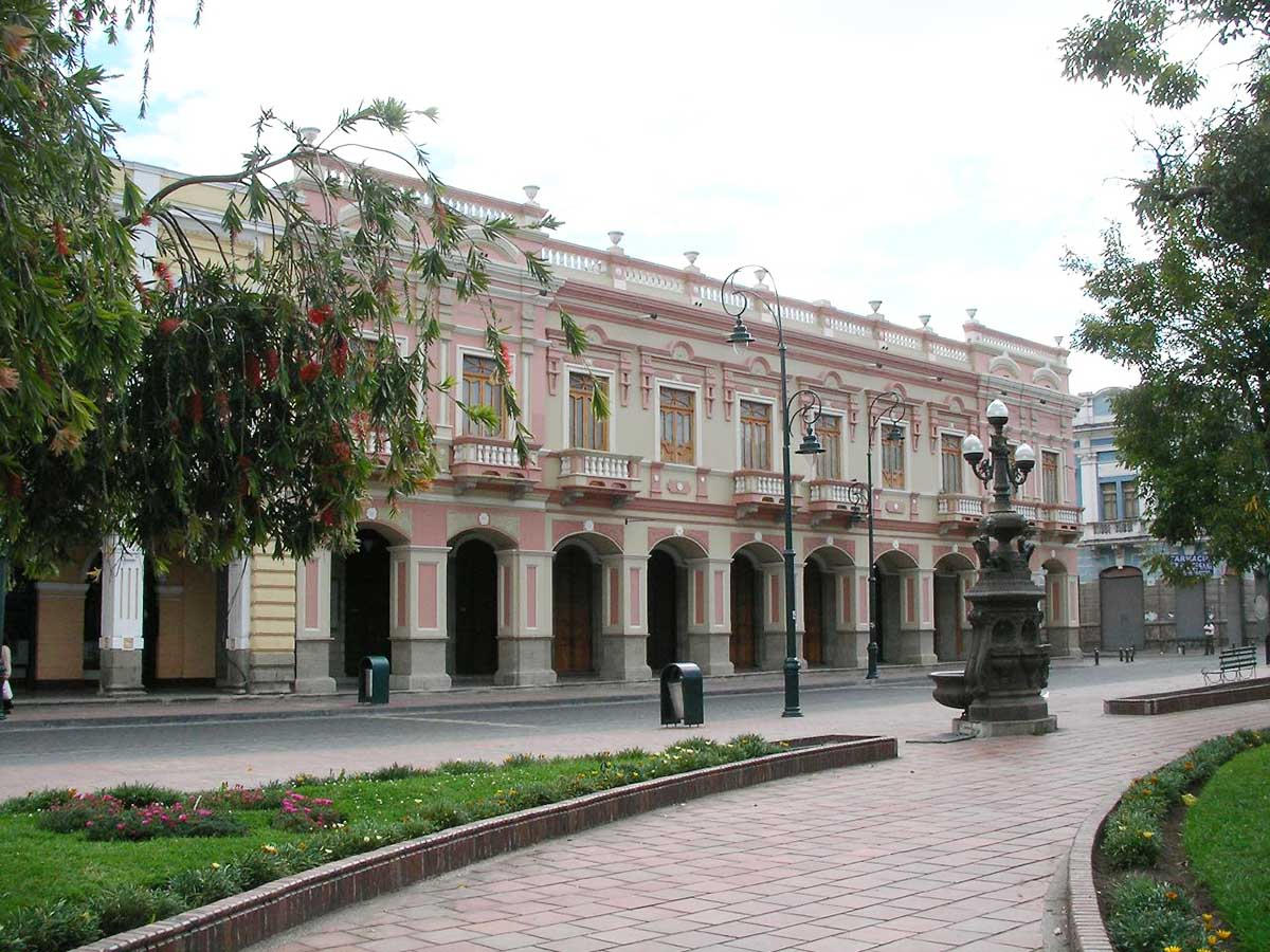 A pink-hued building with an arched arcade on the first level in Riobamba, Ecuador.