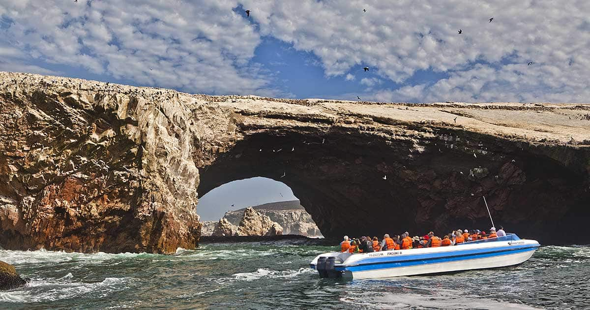 A boat filled with passengers in the ocean around the rocky Ballestas Islands off the coast of Paracas, Peru.