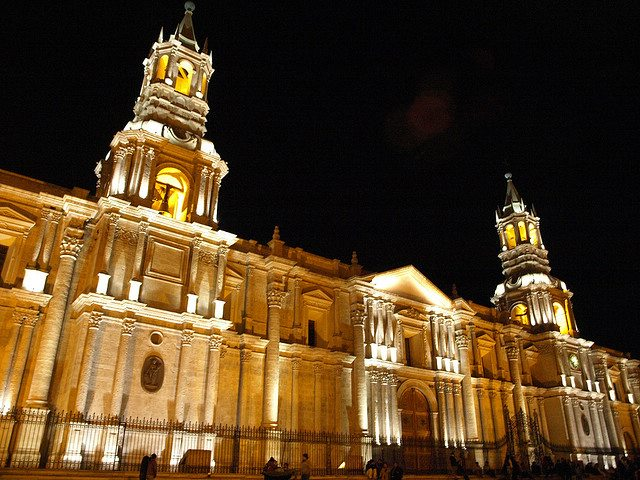 A lit up facade of the Arequipa cathedral, with two tall pillars stretching into the night sky.
