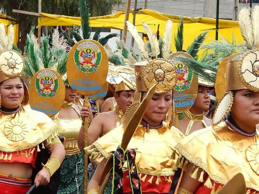 Performers wearing gold and red costumes and headdresses at carnival in the city of Cajamarca.