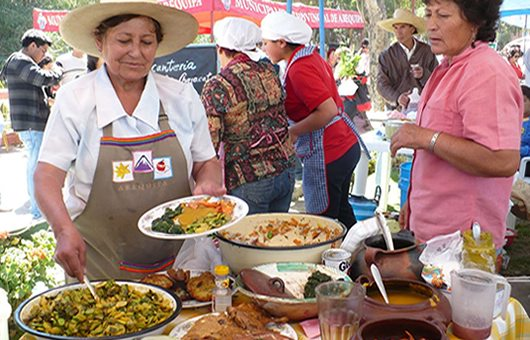 Woman in apron and hat serving traditional Arequipa easter meal