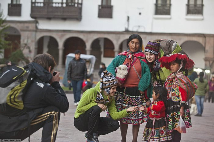 A native Peruvian woman and two children stand with two tourists. A man crouches to take a photo.