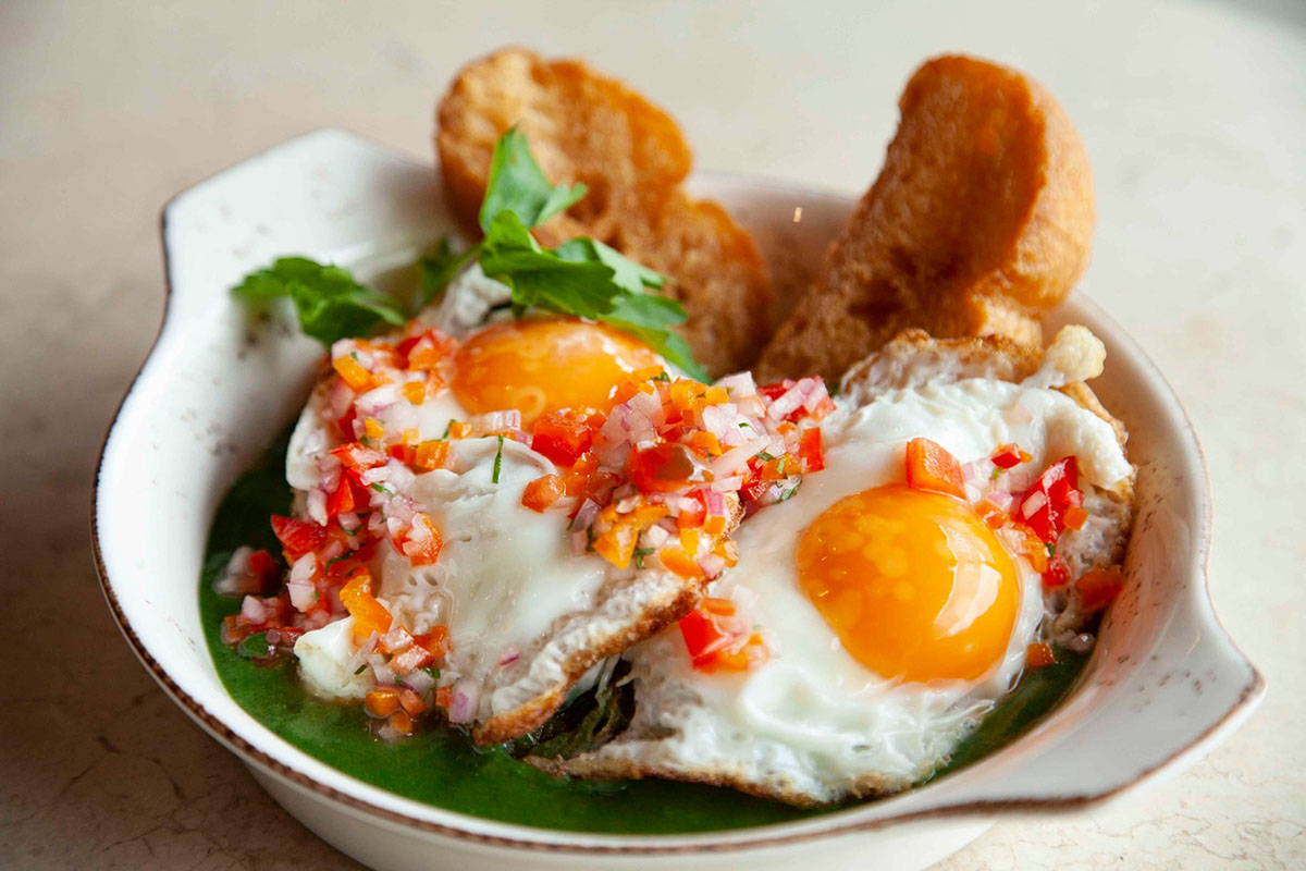 Two fried eggs with spinach pure beneath served with toast and a spicy sauce known as salsa criolla.