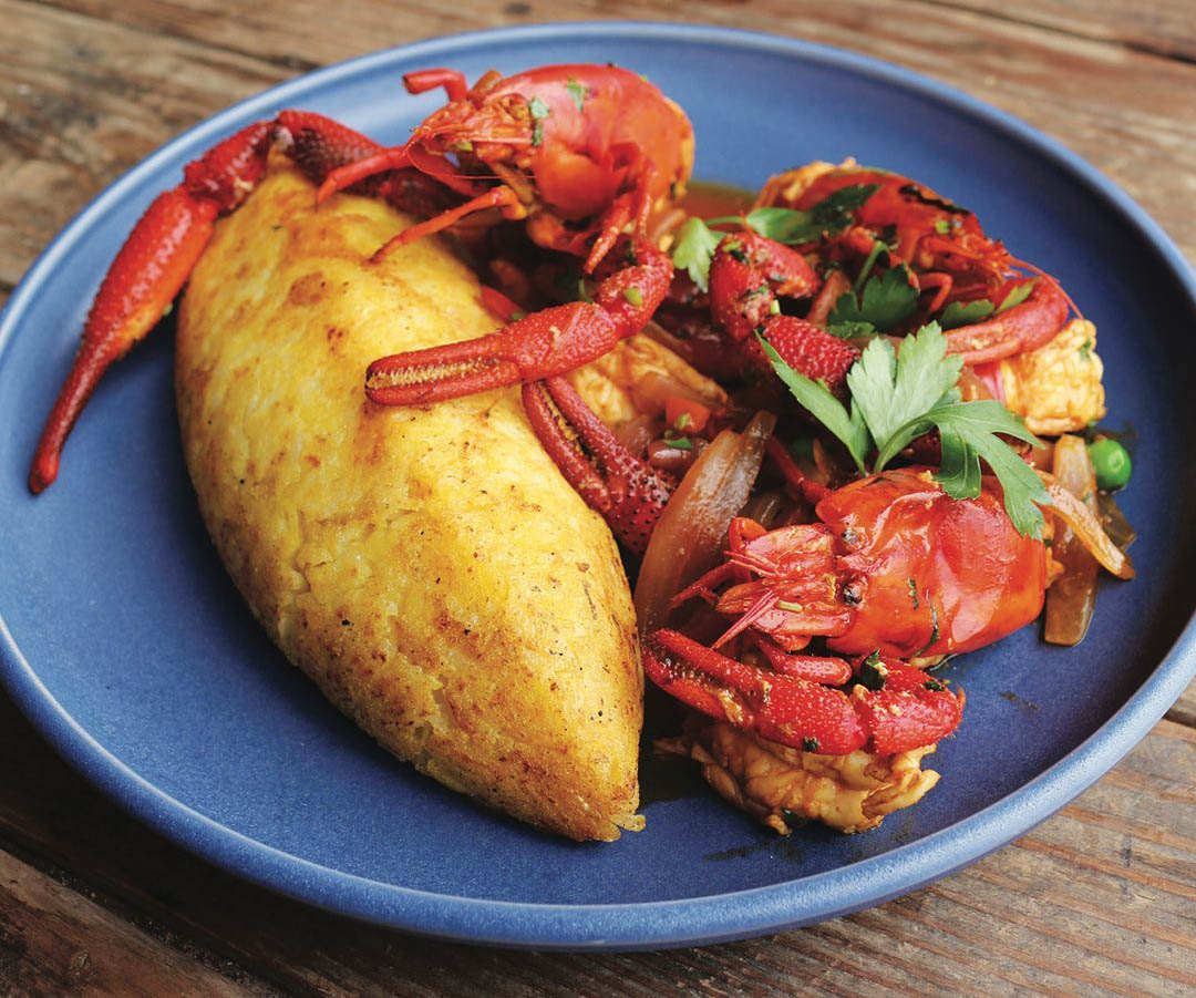 A blue plate with lobster and a fried, stuffed potato at Huaca Pucllana restaurant.