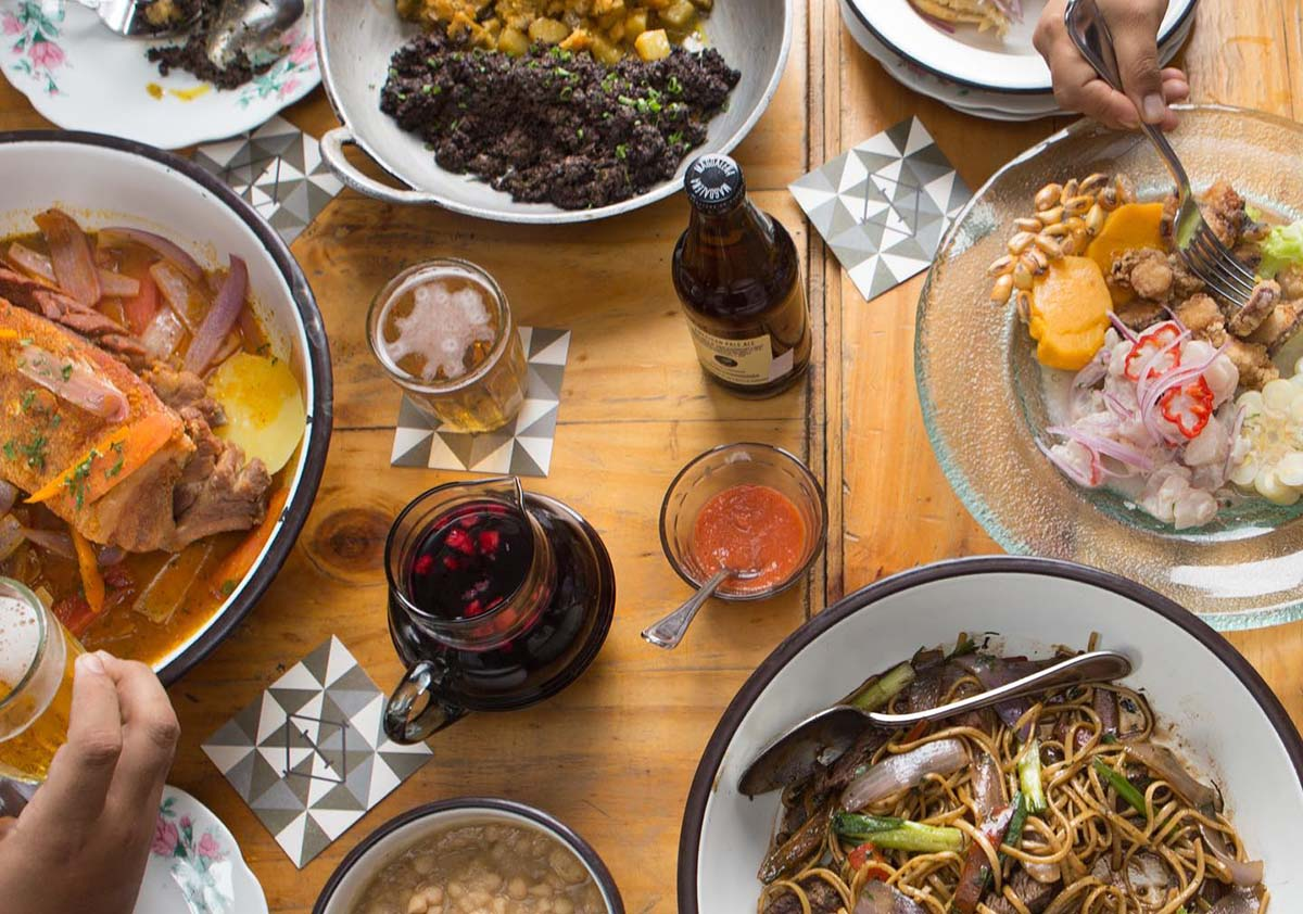 A wooden table covered with various plates, drinks and sauces at Isolina in Lima, Peru.