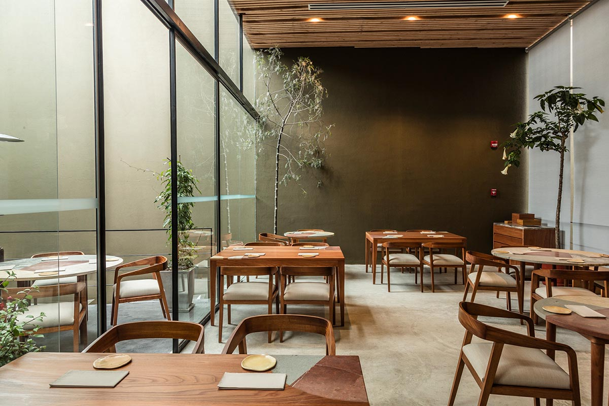 Wooden tables and chairs with a glass wall, wood ceiling, and concrete floors at Kjolle in Lima.