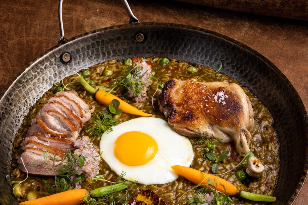 A skillet with various meats, an egg and vegetables at Mayta, one of the best restaurants in Lima.