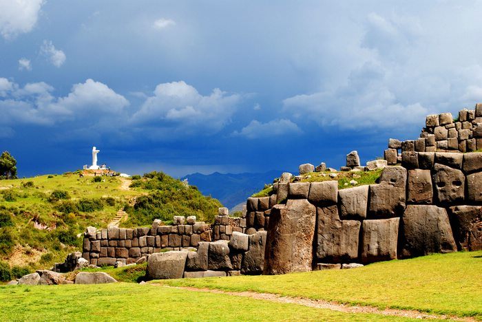 Large stone ruins, Sacsayhuaman in Cusco, with a white christ statue on a hill behind.