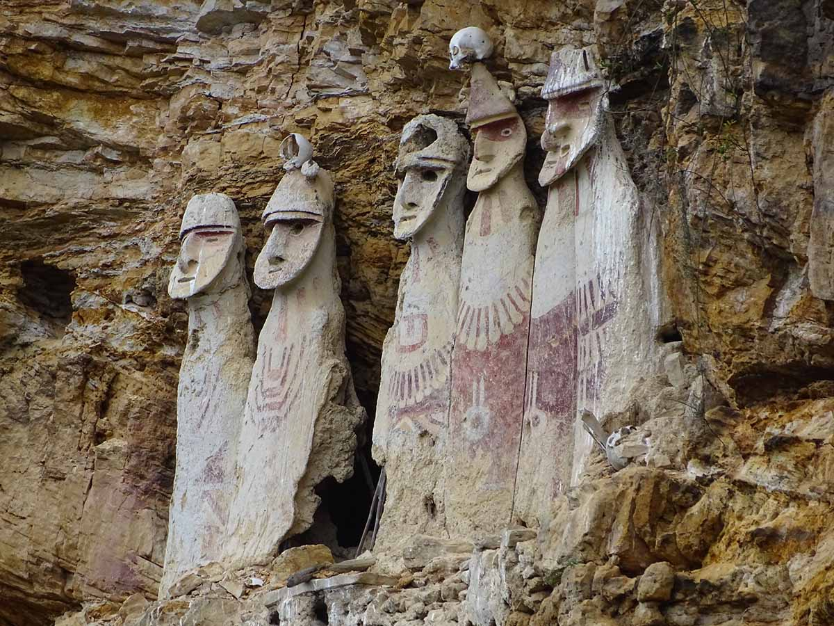 Five sarcophagi with human features embedded in a rocky cliff at Karajia.