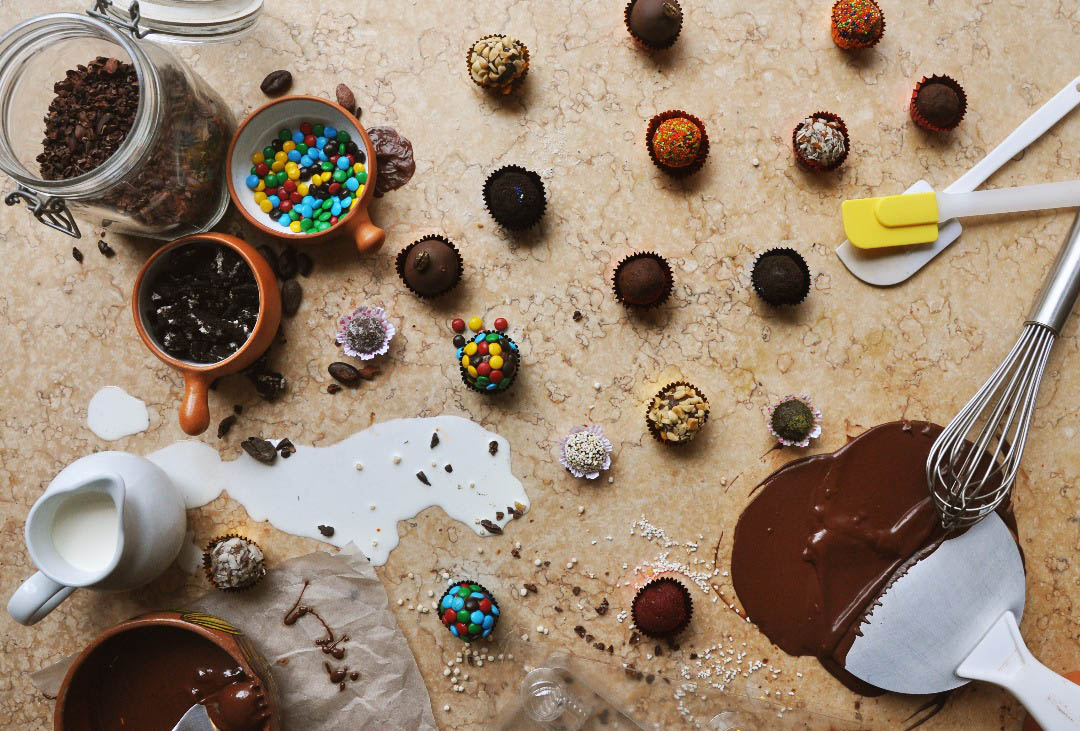 Truffles, varied ingredients and melted chocolate scattered artfully on a table at ChocoMuseo