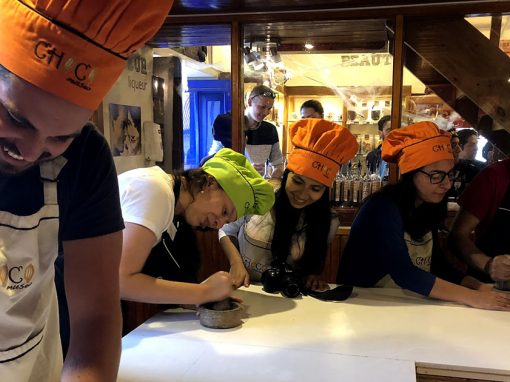 Group of 4 young adults with apron and chefs hat grinding cacao beans during a chocolate-making workshop ChocoMuseo