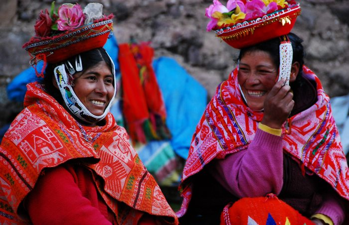 Two Quechua women sitting together in their brightly colored traditional clothing and hats.