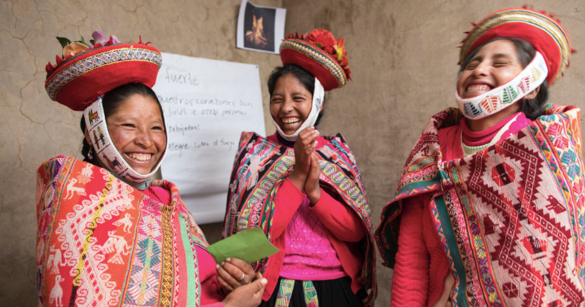 Group of three Andean women in traditional attire taking part in an Awamaki workshop.