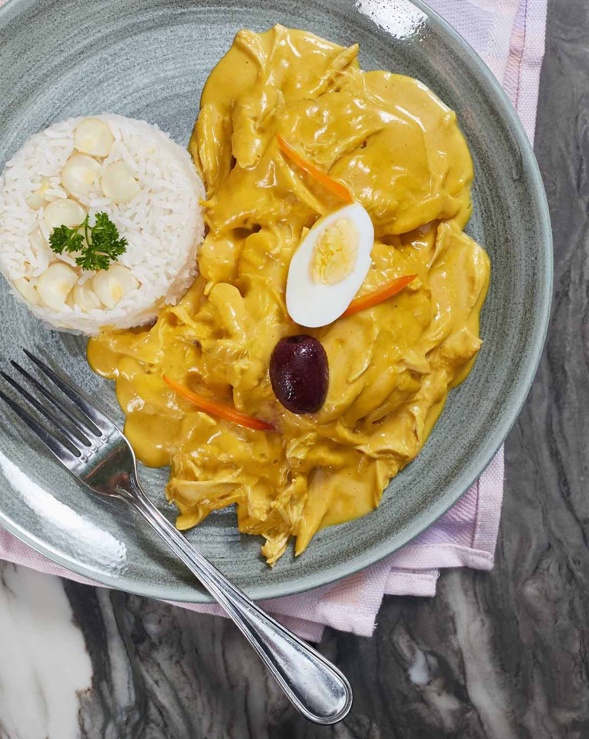 A top Peruvian food, aji de gallina is a yellow chicken stew served with white rice.
