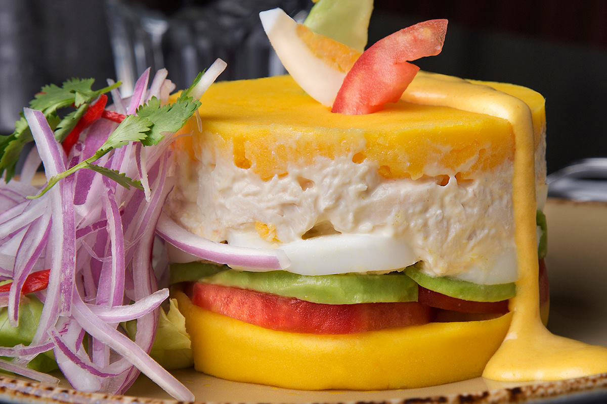 Causa rellena with layers of mashed potato, tomato, avocado, egg, and chicken salad.