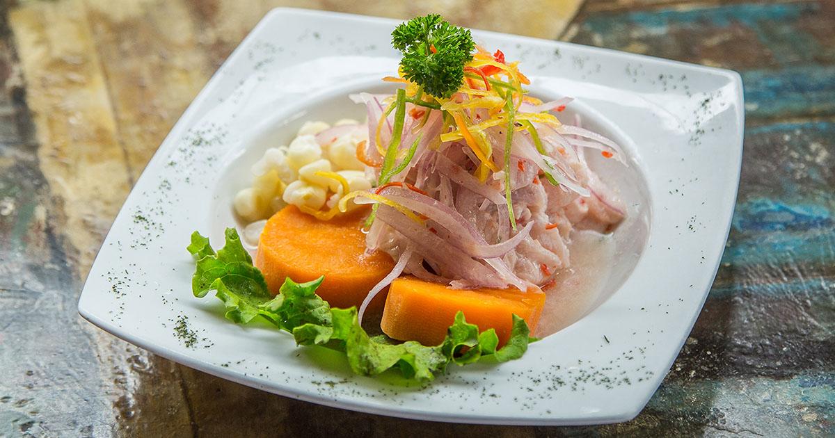 A square dish with ceviche, lettuce, sweet potato, and corn.